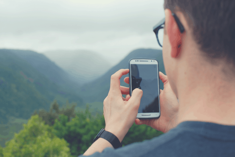 Man looking at phone with mountains in background